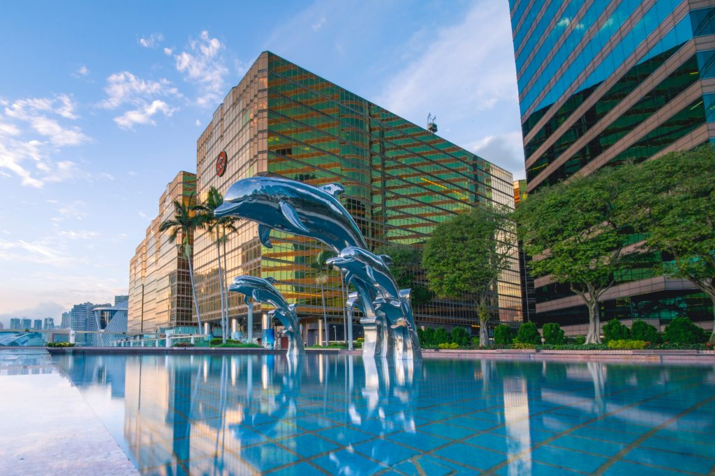 three-blue-dolphins-statue-front-of-water-near-building-1458457